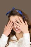 La giovane donna nascosta in mani il fronte Immagine Stock