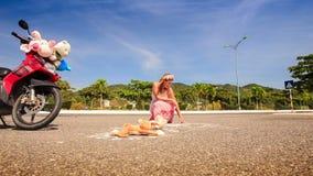 La giovane donna negli edifici occupati lunghi del vestito ed i cerchi giocano su asfalto stock footage