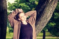 La giovane donna negli sport copre il riposo di un parco dopo un allenamento di mattina Fotografia Stock