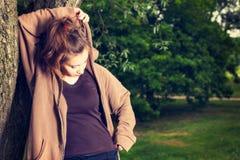 La giovane donna negli sport copre il riposo di un parco dopo un allenamento di mattina Immagini Stock Libere da Diritti