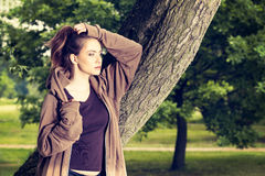 La giovane donna negli sport copre il riposo di un parco dopo un allenamento di mattina Fotografie Stock