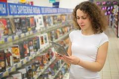 La giovane donna in negozio tiene nel dvd delle mani Immagini Stock