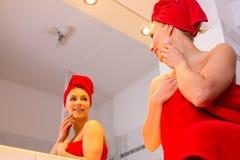 La giovane donna nel bagno esamina uno specchio Fotografia Stock Libera da Diritti