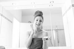 La giovane donna nel bagno esamina uno specchio Immagini Stock Libere da Diritti