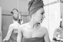 La giovane donna nel bagno esamina uno specchio Fotografie Stock Libere da Diritti