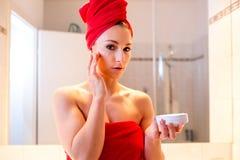 La giovane donna nel bagno esamina uno specchio Fotografia Stock