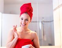 La giovane donna nel bagno esamina uno specchio Immagine Stock Libera da Diritti