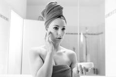 La giovane donna nel bagno esamina uno specchio Immagine Stock
