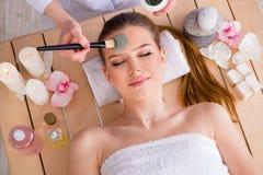 La giovane donna nel concetto di salute della stazione termale con la maschera di protezione fotografia stock libera da diritti