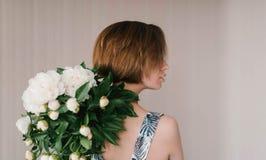 La giovane donna nel mazzo della tenuta del vestito dal fashon di belle peonie bianche fiorisce dietro il suo indietro giorno del Fotografie Stock Libere da Diritti