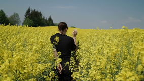 La giovane donna nel nero copre i camici che passa il hd commovente dei fiori del campo giallo archivi video