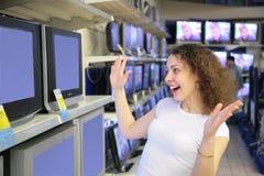 La giovane donna nel piacere esamina le TV in negozio Fotografia Stock