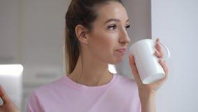 La giovane donna nel t-thirt rosa gode di di bere il tè con il biscotto dell'inverno a casa archivi video
