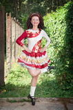La giovane donna nell'Irlandese balla il vestito ed il dancing della parrucca Fotografia Stock