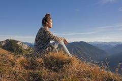 La giovane donna nelle montagne, gode del sole di sera Immagine Stock