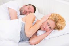 La giovane donna non può dormire a causa del ragazzo che russa Fotografia Stock