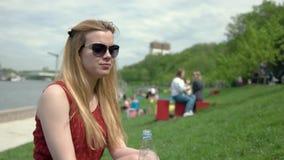 La giovane donna in occhiali da sole beve l'acqua da una bottiglia di plastica il giorno di estate stock footage