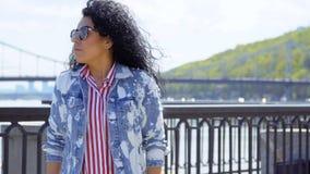 La giovane donna in occhiali da sole considera l'orologio ed aspetta qualcuno all'argine archivi video