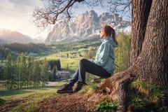 La giovane donna in occhiali da sole e giacca blu sta sedendosi sulla collina fotografia stock