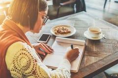 La giovane donna in occhiali sta sedendosi in caffè alla tavola, firmante i documenti La ragazza scrive la penna, compila un'appl Fotografie Stock Libere da Diritti