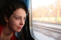 La giovane donna osserva nella finestra del `s del treno immagine stock