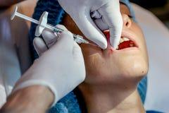 La giovane donna ottiene un'iniezione in sue labbra nel salone di bellezza Immagine Stock Libera da Diritti