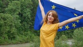 La giovane donna patriottica sta tenendo un'insegna della bandiera di Unione Europea che sorride e che esamina la macchina fotogr video d archivio