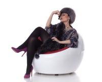 La giovane donna in pelliccia con la ciliegia si siede sulla poltrona. Fotografia Stock Libera da Diritti