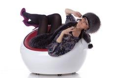 La giovane donna in pelliccia con la ciliegia si siede sulla poltrona. Immagini Stock