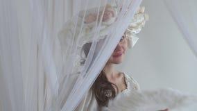 La giovane donna perfetta in cappello di seta con i fiori smazza il suo fronte con il fan della piuma bianca, nascondentesi dietr archivi video