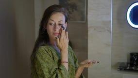 La giovane donna piacevole nei supporti nel bagno dell'hotel, massaggi della camicia da notte affronta a crema stock footage
