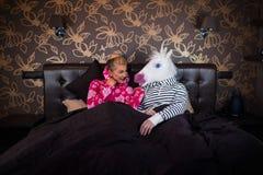 La giovane donna in pigiama si siede sul letto con l'unicorno immagini stock libere da diritti