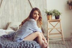 La giovane donna in pigiama sveglia di mattina in camera da letto scandinava accogliente e nella menzogne sul letto con la copert Immagini Stock Libere da Diritti
