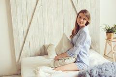 La giovane donna in pigiama sveglia di mattina in camera da letto scandinava accogliente e nella menzogne sul letto con la copert Fotografie Stock Libere da Diritti