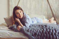 La giovane donna in pigiama sveglia di mattina in camera da letto scandinava accogliente e nella menzogne sul letto con la copert Fotografia Stock Libera da Diritti