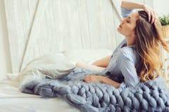 La giovane donna in pigiama sveglia di mattina in camera da letto scandinava accogliente e nella menzogne sul letto con la copert Fotografia Stock