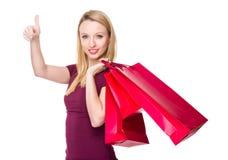 La giovane donna porta con il sacchetto della spesa ed il pollice su Immagini Stock Libere da Diritti