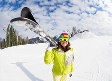 La giovane donna porta lo sci della montagna sulla località di soggiorno dell'inverno Immagine Stock