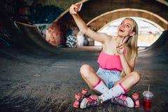 La giovane donna positiva è sedentesi e prendente il selfie Sta mostrando il simbolo del pezzo con le sue dita Inoltre c'è a fotografia stock