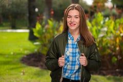 La giovane donna positiva sorride e esamina la macchina fotografica immagine stock