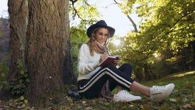 La giovane donna premurosa che fa una certa nota nel suo attimo del taccuino si siede sul gteen l'erba nel parco della città video d archivio