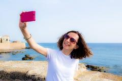 La giovane donna prende il selfie nella parte anteriore al mare con uno smartphone Immagini Stock Libere da Diritti