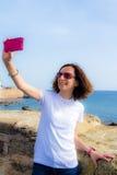 La giovane donna prende il selfie nella parte anteriore al mare con uno smartphone Fotografie Stock Libere da Diritti