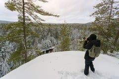 La giovane donna prende la foto nell'inverno Fotografia Stock Libera da Diritti
