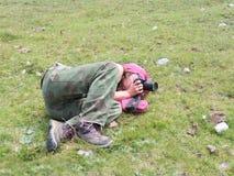 La giovane donna prende le immagini che pongono il prato fotografia stock libera da diritti