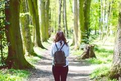 La giovane donna prende una foto con lo Smart Phone su una via nella foresta Fotografie Stock Libere da Diritti