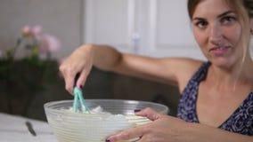 La giovane donna prepara gli ingredienti di miscelazione della pasta nella ciotola facendo uso di sbatte nella cucina e nello sgu archivi video