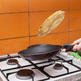 La giovane donna produce i pancake secondo una ricetta tradizionale immagini stock libere da diritti