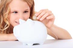 La giovane donna risparmia i soldi in porcellino salvadanaio Fotografie Stock