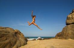 La giovane donna salta dalle rocce Fotografia Stock Libera da Diritti